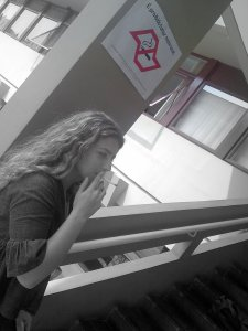 Estudante fuma em local que pela nova lei é proibido, mesmo sendo ao ar livre.